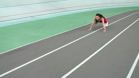 Sporty girl working out in sportswear on sport stadium. Sexy girl doing push ups Live Action