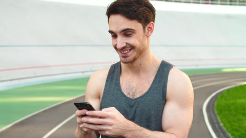 Closeup runner standing with smartphone on track. Sporty man holding phone Live Action