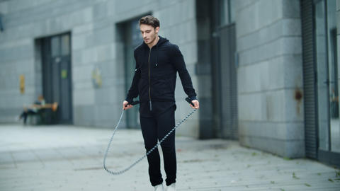 Fit man training jump exercise on skipping rope on workout. Sporty man jumping Live Action