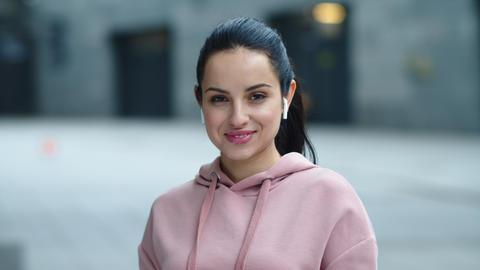 Young woman listening music in headphones outdoor. Portrait woman in earphones Live Action