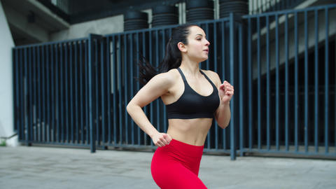 Attractive female runner jogging outdoor. Close up fitness woman training run Live Action
