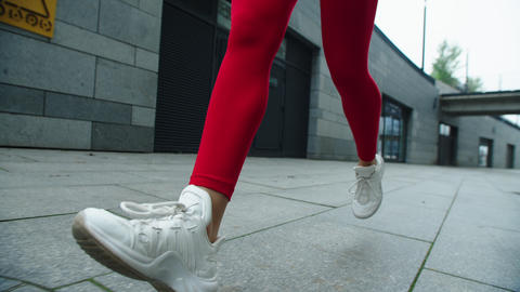 Woman legs running on street in slow motion. Close up female runner legs jogging Live Action