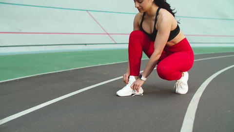 Sport woman lacing up sneakers for workout on track. Woman runner tying up shoes Live Action