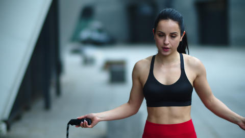 Closeup fit woman jumping on skip rope outdoor. Tired woman finishing exercise Live Action
