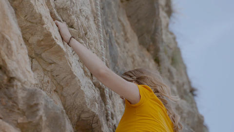 A female rock climber climbs up a rock. Learning to climb Stock Video Footage