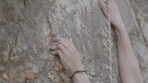 A female rock climber climbs up a rock. Learning to climb Footage