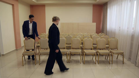 A man and a woman move the chairs in the conference room Footage