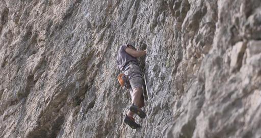 Male rock climber climbs up a rock Footage