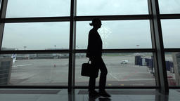 Bored looking business man silhouette, pace against glass wall terminal window Footage