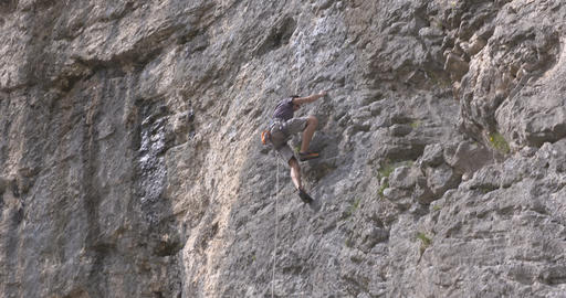 Male rock climber climbs up a rock Footage