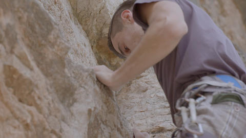 Male rock climber climbs up a rock Live Action
