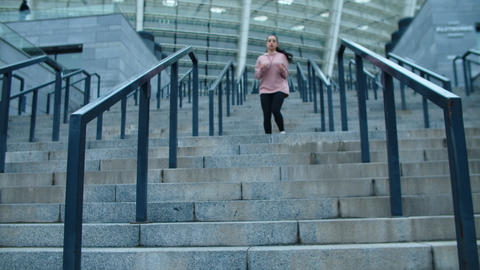 Sporty woman running down stairs outdoor. Runner woman…, Live Action
