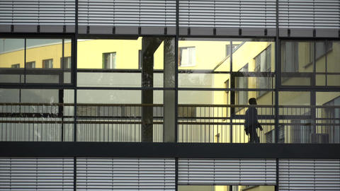 Silhouette Of A Person Walking Inside A Building. Exterior of modern office Live Action