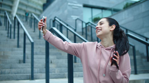 Closeup smiling woman posing for selfie photo outdoor. Young woman touching hair Live Action