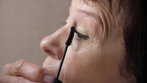 Elderly woman paints her eyelashes Live Action