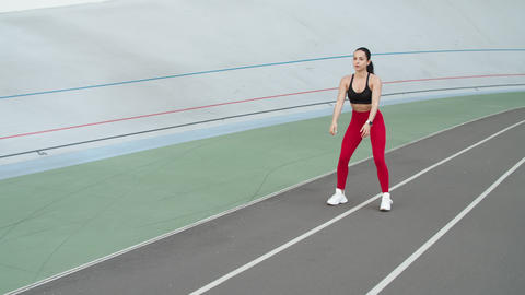 Sporty woman exercising outdoor at stadium. Fitness girl doing squat exercises Live Action