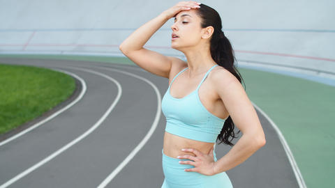 Attractive woman runner taking rest after running workout on racetrack Live Action