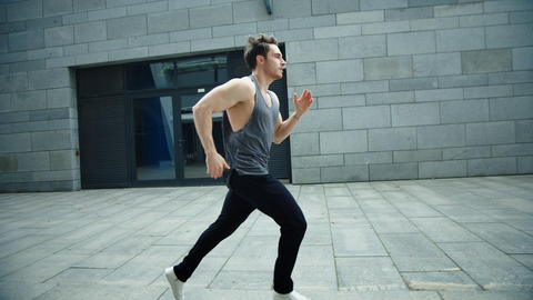 Fitness man running on urban street in slow motion. Male runner jogging outdoor Live Action