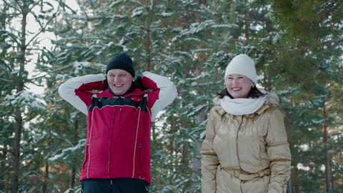 Cheerful couple laughing in winter forest on snowy trees landscape. Happy man Live Action