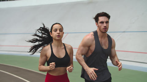 Fitness couple running on athletics track. Sport couple training together Live Action