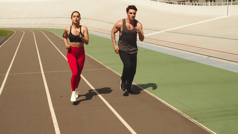 Fitness couple training together at stadium. Sport couple running together Live Action