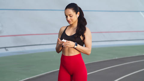 Sporty woman wearing earphones on modern track. Sexy girl using wireless headset Live Action