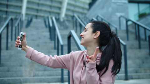 Happy woman making photo on smartphone outside. Sporty woman making selfie photo Live Action