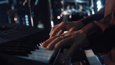 Hands of male musician playing at synthesizer. Mens arms plays solo of music or Live Action