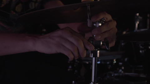 Close up of the hands of a drummer. A man sets the drums before a live Live Action