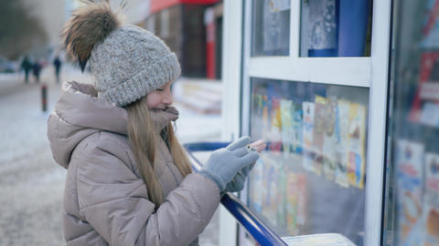 Teenager girl buying ice cream in street kiosk on winter walk. Happy girl buyer Live Action