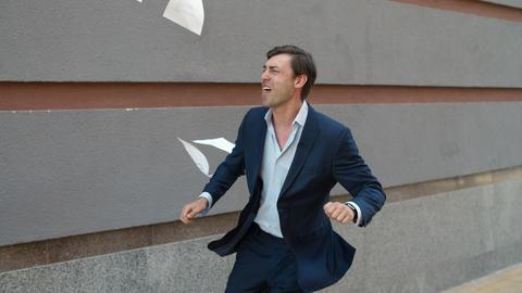 Joyful businessman celebrating victory. Happy man throwing documents outdoor Live Action