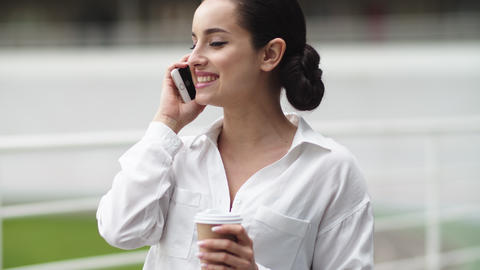 Business woman talking phone outdoor. Girl drinking coffee on break outdoor Live Action