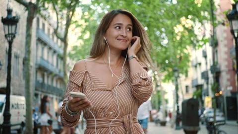 Portrait of sexy woman dancing in earphones. Girl relaxing with music outdoor Live Action