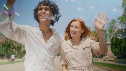 Portrait of love couple catching soap bubbles. Romantic man and woman having fun Live Action