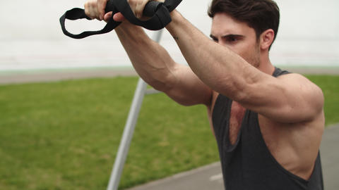 Close up fit man training outdoors with trx fitness strap at stadium Live Action