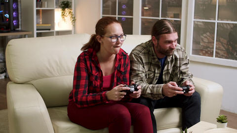 Cheerful young couple celebrating their victory while playing video games Live Action