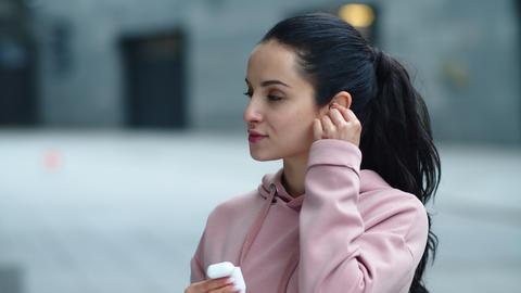 Closeup smiling woman wearing wireless earbuds. Sporty woman enjoying music Live Action