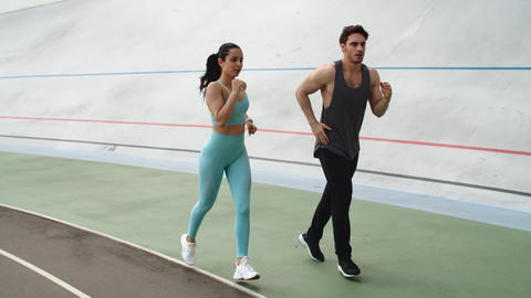 Fitness couple training together at modern stadium. Sporty couple running Live Action