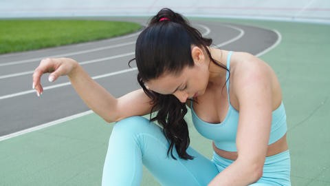 Tired woman runner resting after workout on track. Portrait of exhausted woman Live Action