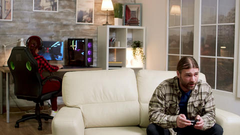Upset man throwing wireless controller on the couch Live Action