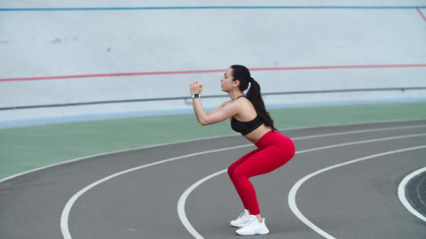 Woman exercising on workout at track. Woman training workout outdoor at stadium Live Action