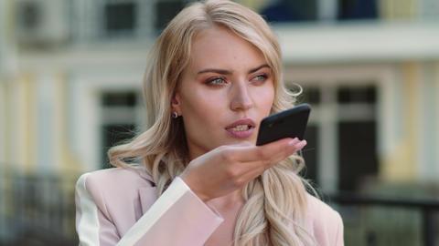Business woman recording voice messages. Woman recording audio message on phone Live Action