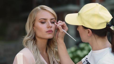 Closeup model preparing for filming. Make up artist doing makeover at street Live Action