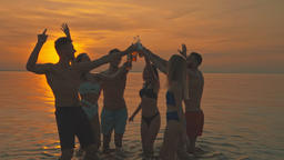 The happy friends clink bottles against the beautiful sunset. slow motion Live Action
