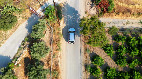 Overhead view of crossover SUV car driving along the empty gravel countryside village road Live Action