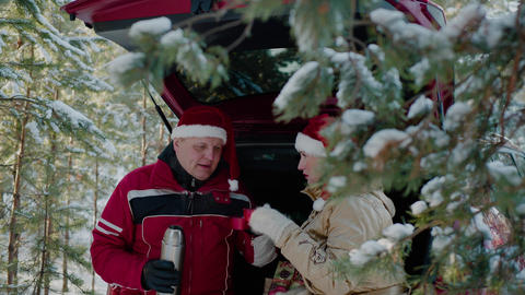 Cheerful couple in santa hats drinking hot tea in winter forest Live Action