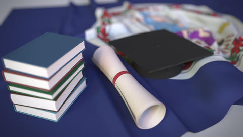 Graduation cap, books and diploma on the flag of Virginia. Higher education in Live Action