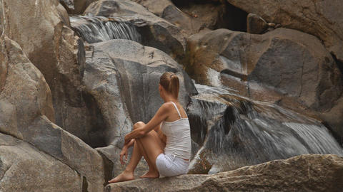 Backside Blond Girl Sits on Stone Looks at Waterfall Footage