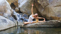 Blond Girl from Pose Half-Lotus Bends to Foot on Stone Live影片