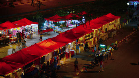 VIENTIANE. LAOS - CIRCA DEC 2013: Shoppers browse the well lighted vendor stands Footage